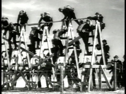 trainees climbing over ladder obstacle course. climbing over wall from ditch. over wire obstacles. physical stamina endurance military wwii. - endurance stock videos & royalty-free footage