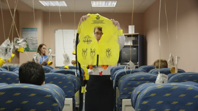 trainees in aviation cabin crew class demonstrating the exits and donning of life vests with female instructor in background looking on, red r3d 4k - aerospace stock videos & royalty-free footage
