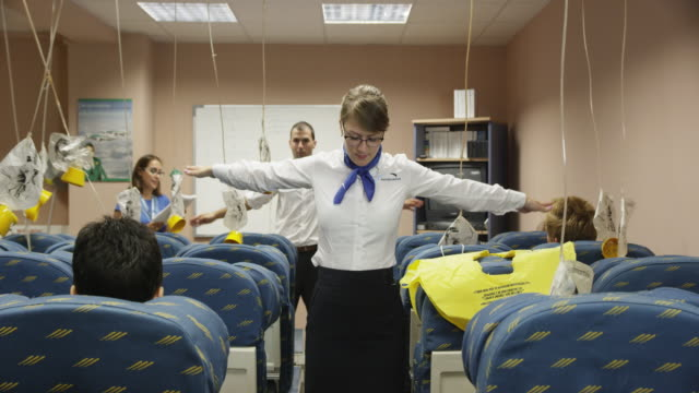 trainees in aviation cabin crew class demonstrating the exits and donning of life vests with female instructor in background looking on, red r3d 4k - crew stock videos & royalty-free footage