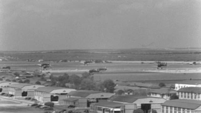 trainer airplanes fly and land over kelly field in san antonio, texas in 1940. - 1940 video stock e b–roll