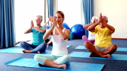 Trainer assisting senior citizens in practicing yoga