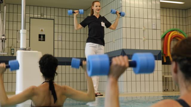 Trainer assisting women at aqua health club