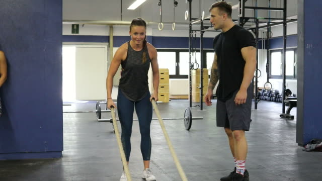 trainer clapping for woman exercising with ropes - shaky stock videos & royalty-free footage