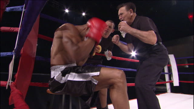 LA MS Trainer giving pep talk to boxer in ring while another man pours water into his mouth and wipes his face / Jacksonville, Florida, USA