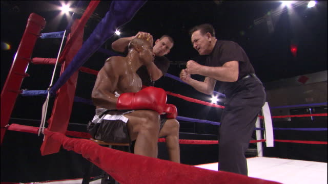 la ms zi cu trainer giving pep talk to boxer in ring while another man wipes his face and pours water over his head / jacksonville, florida, usa - ボクシング点の映像素材/bロール