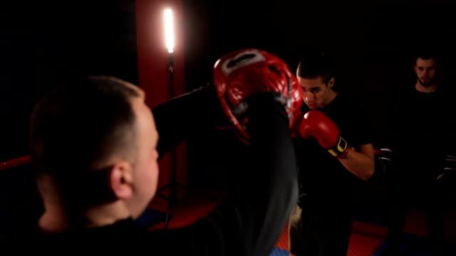 vídeos de stock, filmes e b-roll de treinador praticando com chute boxer - posição de combate