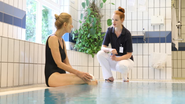 Trainer talking to woman at poolside in aqua gym