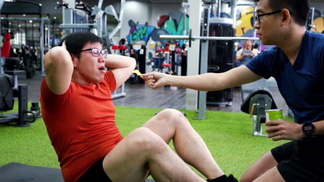 trainer mit chips für anreiz oder motivieren große build-mann zu tun sitzen in der turnhalle - komiker stock-videos und b-roll-filmmaterial