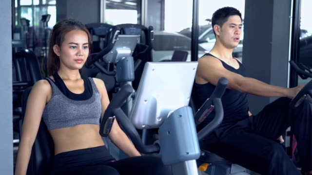 trainer with client on exercise bike machine. - aerobics stock videos and b-roll footage