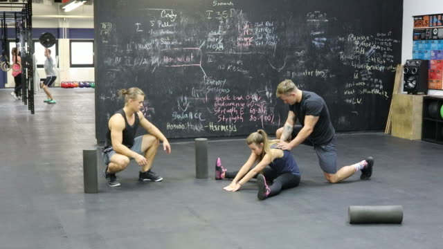 trainers assisting woman in stretching legs at gym - legs apart stock videos and b-roll footage