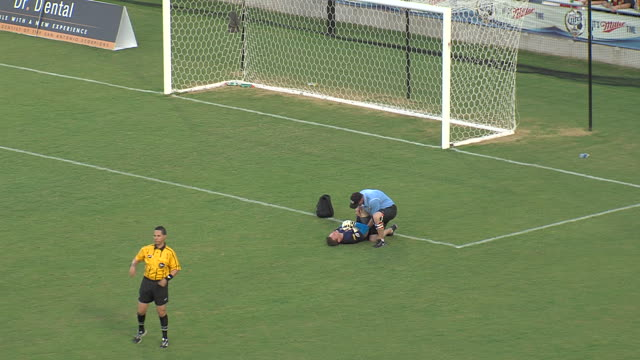 Trainers attend to an injured goalie during a soccer match