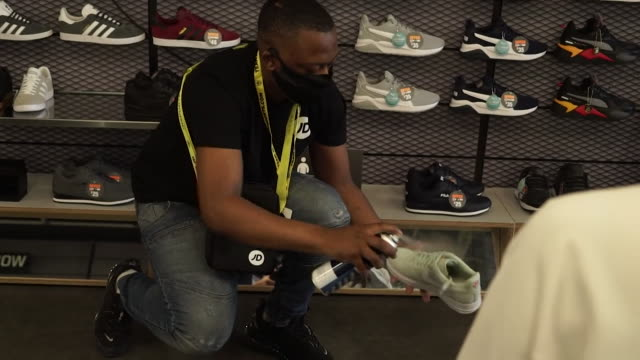 trainers sanitised before and after they have been tried on in jd sports, as clothes shops reopen as coronavirus lockdown restrictions ease - opening stock videos & royalty-free footage