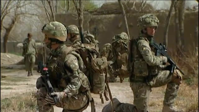 training afghan troops for takeover continues afghanistan helmand province ext british troops along road on patrol soldier on patrol past derelict... - hands behind back stock videos and b-roll footage