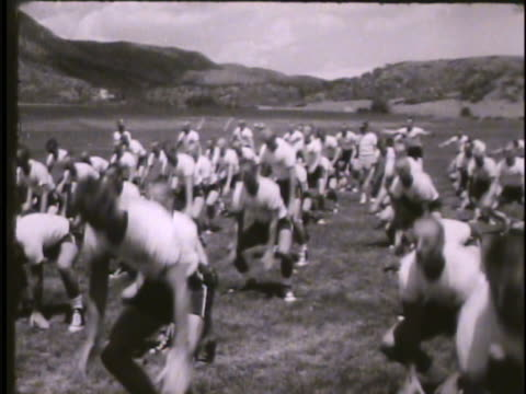 Training instructor shouting instructions cadets on field performing squats jumping jacks upper classmen supervising Physical training PT Colorado CO...