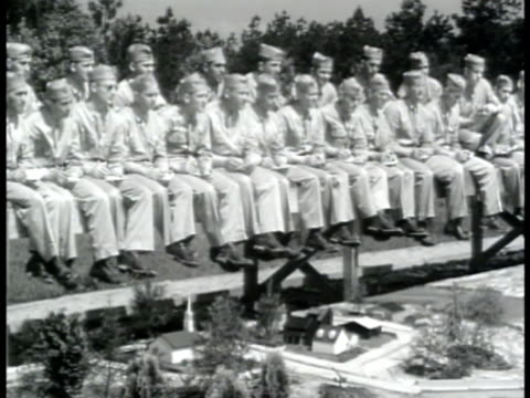 stockvideo's en b-roll-footage met training officer in large model mock up town soldiers sitting side benches taking notes vs model w/ buildings marked signs for unit kitchen front... - 1943