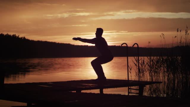 桟橋での訓練サンセットレイクスクワット - リフレクション湖点の映像素材/bロール