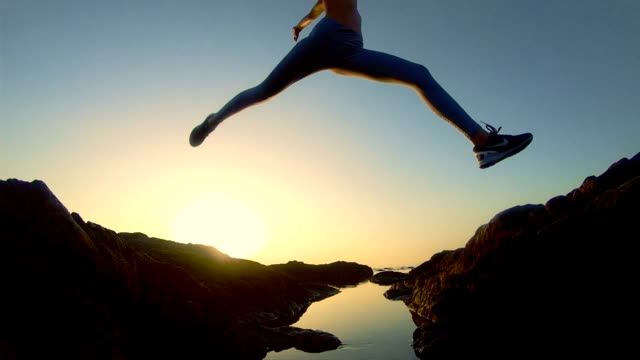 training on a rocky shore. epic jump - sportswear stock videos & royalty-free footage