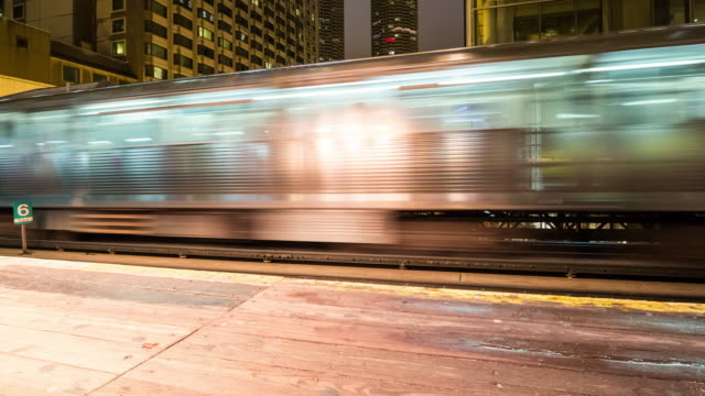 Trains and Riders Passing Through a Downtown Chicago Train Station at Night