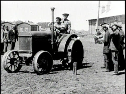 a train's cargo of tractors / russian men inspect a device / the device smokes / a man detaches a steering wheel / an observer smokes a cigarette and... - tractor stock videos & royalty-free footage