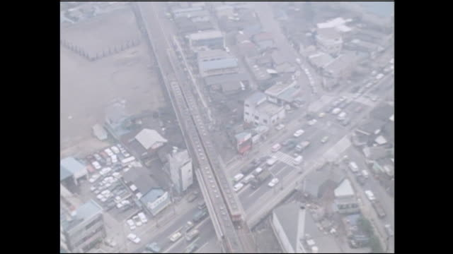 trains cross a railway bridge over a traffic jam on keiyo expressway in tokyo, japan. - 大気汚染点の映像素材/bロール
