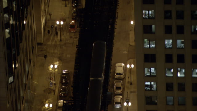 l trains cross between high-rise buildings in chicago, illinois, at night. - chicago 'l' stock videos & royalty-free footage