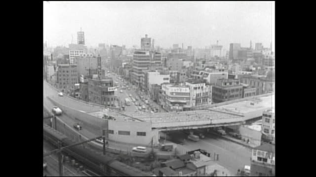 Trains leave from Shimbashi Station; beams extend over the top of the Shuto Expressway during construction.