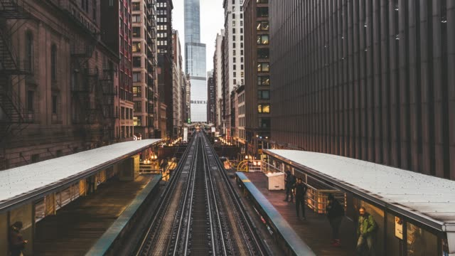 t/l pan trains passing over tracks in downtown chicago - chicago 'l' video stock e b–roll