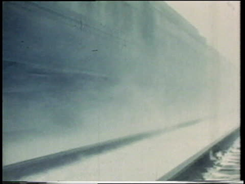 1941 MONTAGE Trains racing along track blowing snow into the air and sounding off whistle / United States