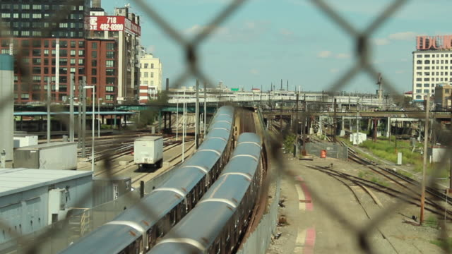 trains through a chain link fence in queens nyc - kettenglied stock-videos und b-roll-filmmaterial