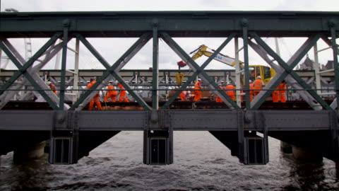vidéos et rushes de trains workers on bridge engineers repair track - reconstruction