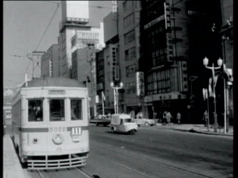 vídeos de stock e filmes b-roll de tram along in street / billboard outside building says 'elia kazan's america america' / exterior of cinema with billboard advertising the film... - 1964