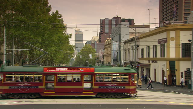 WS Tram and cars moving on street with buildings beside / Melbourne, Victoria, Australia