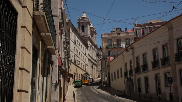 WS Tram and cars on narrow old town street / Lisbon, Portugal