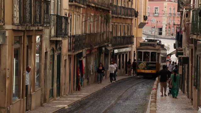 ws tram and cars on narrow old town street / lisbon, portugal - narrow stock videos and b-roll footage