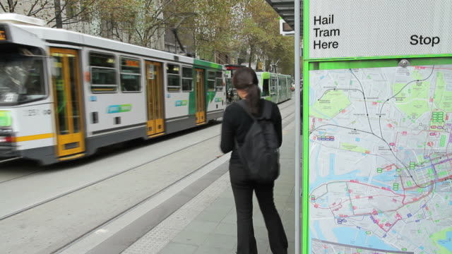 MS T/L Tram and commuters at tram stop / Melbourne, Victoria, Australia