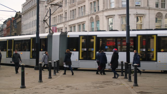 a tram and pedestrians pass by on a busy street in manchester - tram stock videos & royalty-free footage