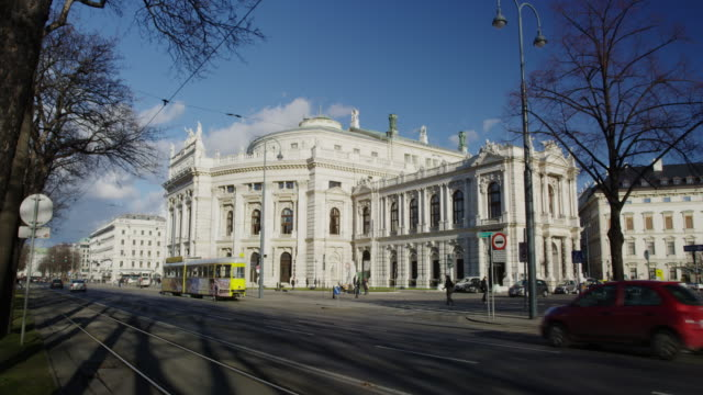 tram and traffic going torwards the austrian national theatre (burg theater) - ウィーン点の映像素材/bロール