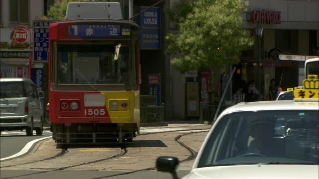 a tram and vehicles travel along a busy road in nagasaki.  - 路面軌道点の映像素材/bロール