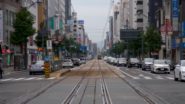 a tram approaches down a street car line in the city of hiroshima in japan. cars drive past the camera on both sides and cross the busy street as the tram comes into view. - hiroshima prefecture stock videos and b-roll footage