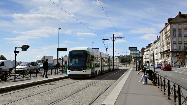 a tram arrives at a stop in the city of nantes. - nantes stock-videos und b-roll-filmmaterial