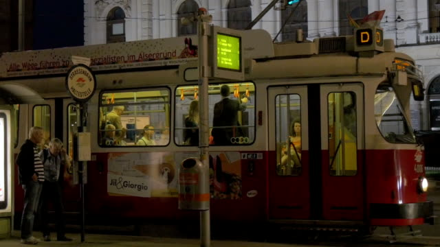 tram at night exiting station outside burg theatre - tram stock-videos und b-roll-filmmaterial