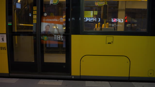 tram doors close and leaves berlin hackescher markt station, young people crossing road early evening - markt video stock e b–roll