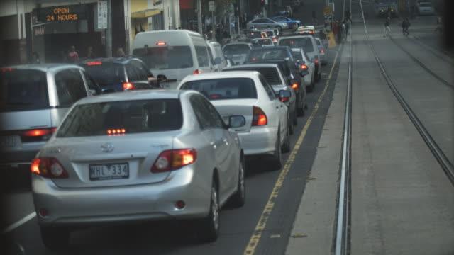 vídeos de stock, filmes e b-roll de t/l pov tram driving down busy street, melbourne, victoria, australia - ponto de vista de bonde