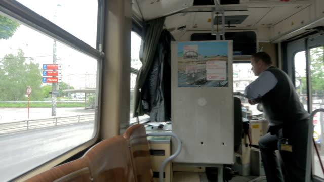 vídeos de stock, filmes e b-roll de tram interior with driver.pan r to l.wide shot. - ponto de vista de bonde