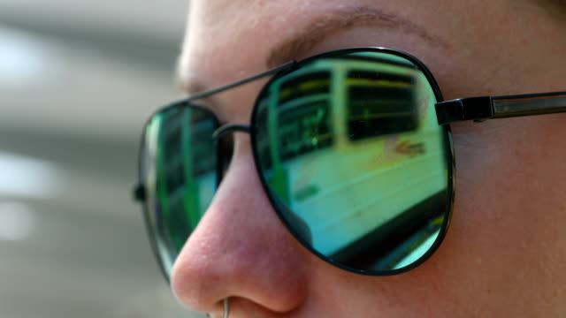 a tram is reflected in the sunglasses of a passenger as she waits for a tram on st kilda road shots of melbourne's iconic transport system taken on... - straßenbahnstrecke stock-videos und b-roll-filmmaterial