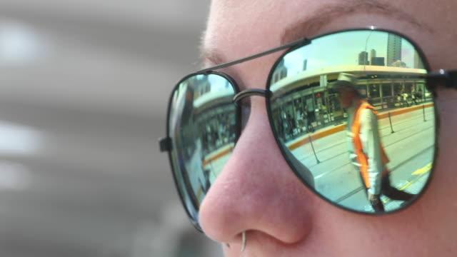 vídeos y material grabado en eventos de stock de a tram is reflected in the sunglasses of a passengers as she waits for a tram on st kilda road on december 1 2016 in melbourne australia - vía de tranvía