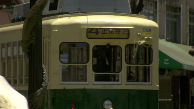 A tram moves along a street in central Nagasaki.