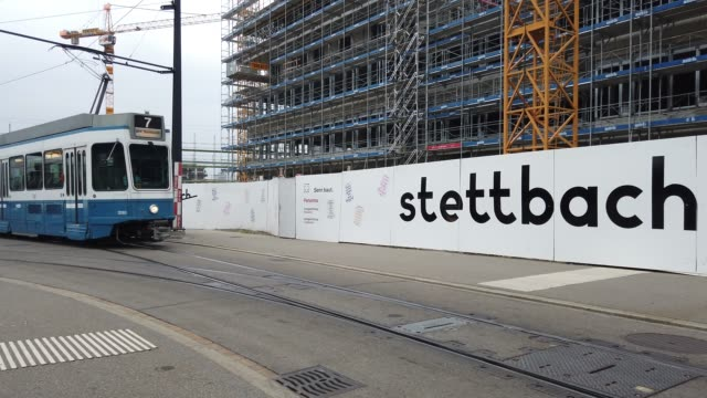 a tram moving through stettbach station in zurich swiss in the background building work in the area - trolleybus stock-videos und b-roll-filmmaterial