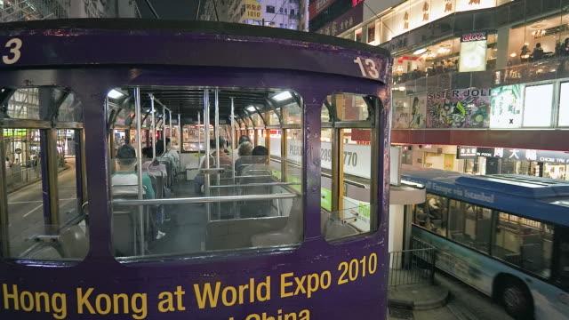 vídeos de stock, filmes e b-roll de t/l pov tram on city streets at night / hong kong, china - ponto de vista de bonde