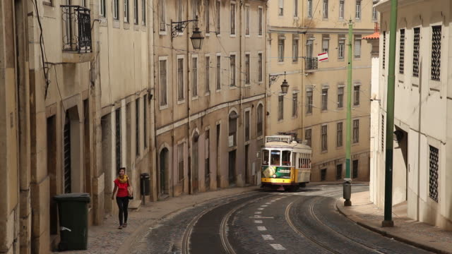 ws tram on narrow old town street / lisbon, portugal - narrow stock videos and b-roll footage